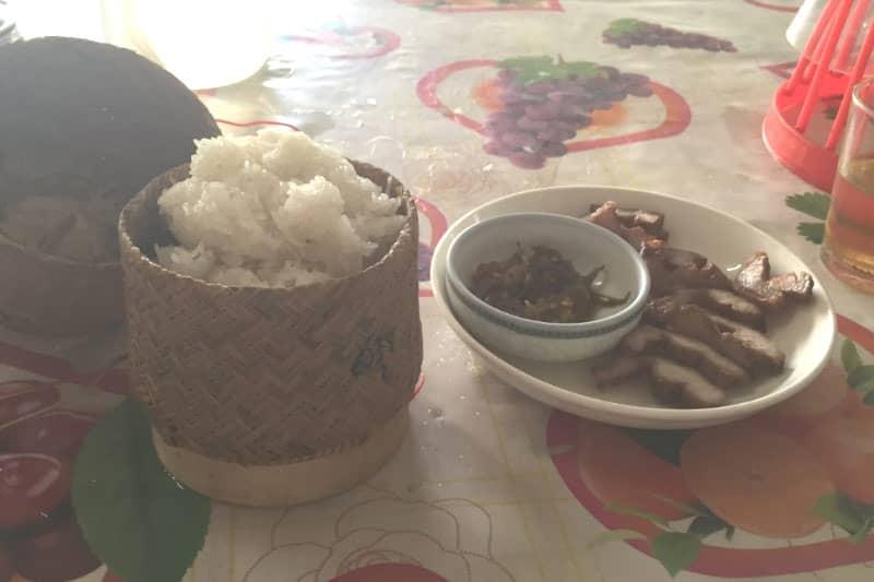 食堂で食べるラオス料理。カゴに入っているのはもち米、おかずは鶏のから揚げです。