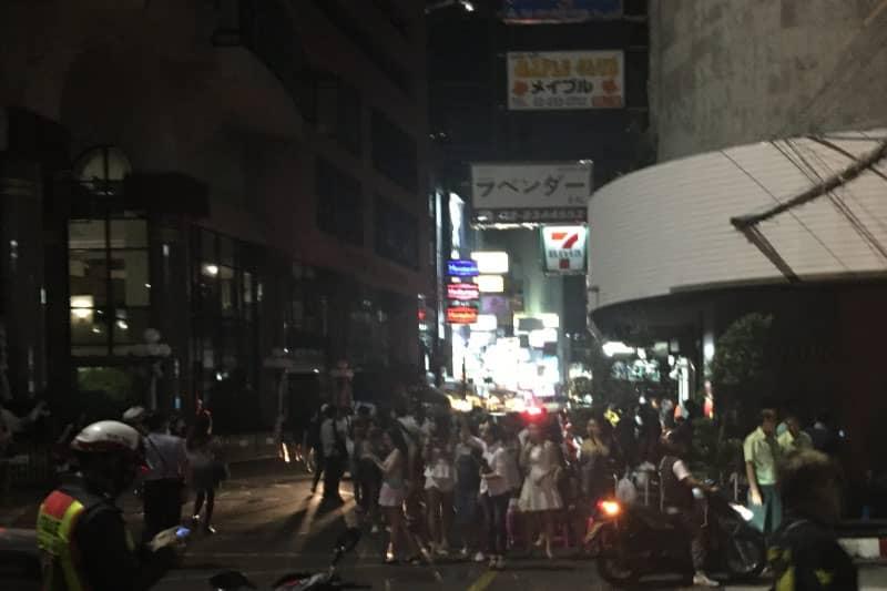 通りの右側手前はすべて停電しています。様子を見に来たカラオケ店のホステスら。