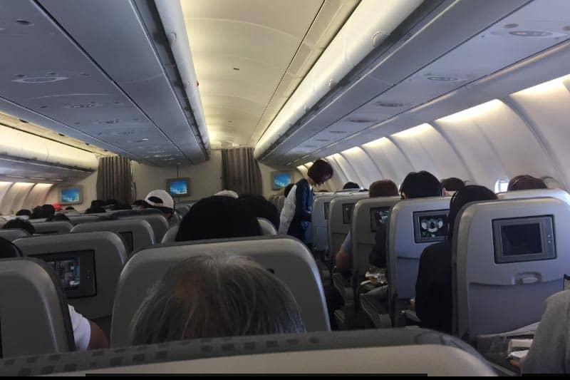 飛行機の中。テレビモニターが前の座席についています。
